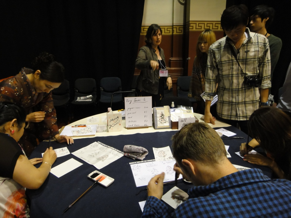 People of all races trying their hand at Japanese ink painting. All hard at work on their own. Photo by Sue Chen.