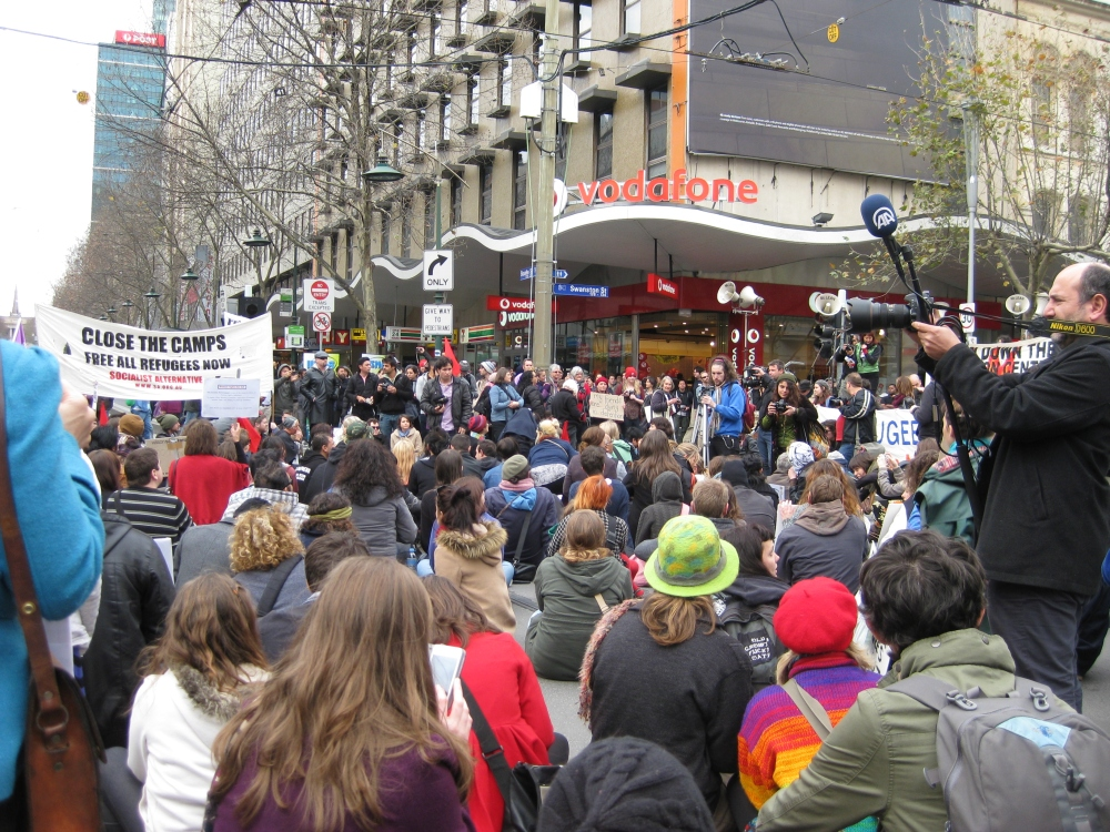 Protestors sitting on the road and voicing their opinions at Swanston St/Bourke St. Photo: Mabel Kwong
